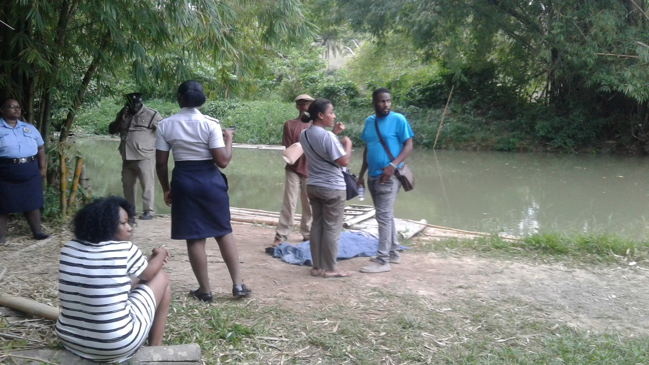 A section of the scene on Thursday during the wait to recover the bodies of a boy and a raft captain who drowned while rafting in the Martha Brae River in Trelawny on Tuesday.