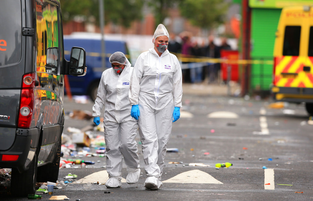 Forensic officers at the scene in the Moss Side area of Manchester, England, where several people have been injured after a shooting, early Sunday Aug. 12, 2018. Police in Manchester say 10 people have been hospitalized as the result of a shooting after a Caribbean carnival in the city. (Peter Byrne/PA via AP)