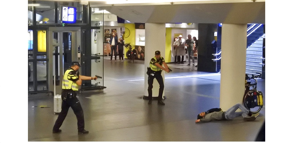 Dutch police officers point their guns at a wounded 19-year-old man who was shot by police after stabbing two people in the central railway station in Amsterdam, the Netherlands, Friday Aug. 31, 2018.