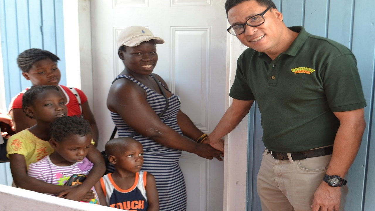 Roger Lyn, Director of Marketing & Corporate Affairs at Rainforest Seafoods shakes hand with a past recipient of a Food for the Poor home.
