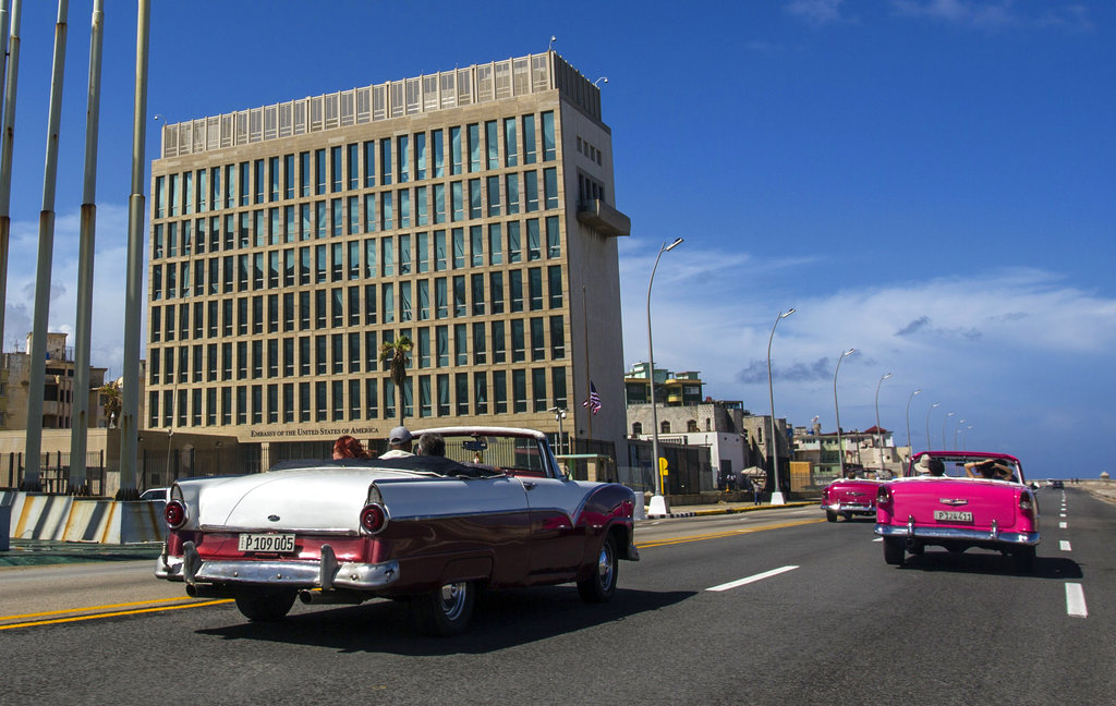 Tourists ride classic convertible cars on the Malecon beside the United States Embassy in Havana, Cuba. (AP Photo/Desmond Boylan, File)