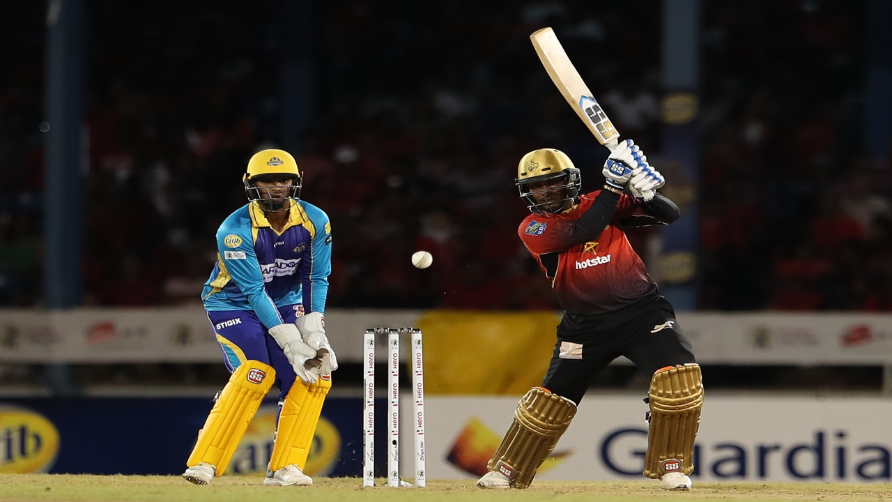 Denesh Ramdin of Trinbago Knight Riders hits four as Nicholas Pooran of Barbados Tridents looks on during their Hero Caribbean Premier League match at Queen's Park Oval on September 7, 2018 in Port of Spain, Trinidad And Tobago. (PHOTOS: CPL via Getty Images).