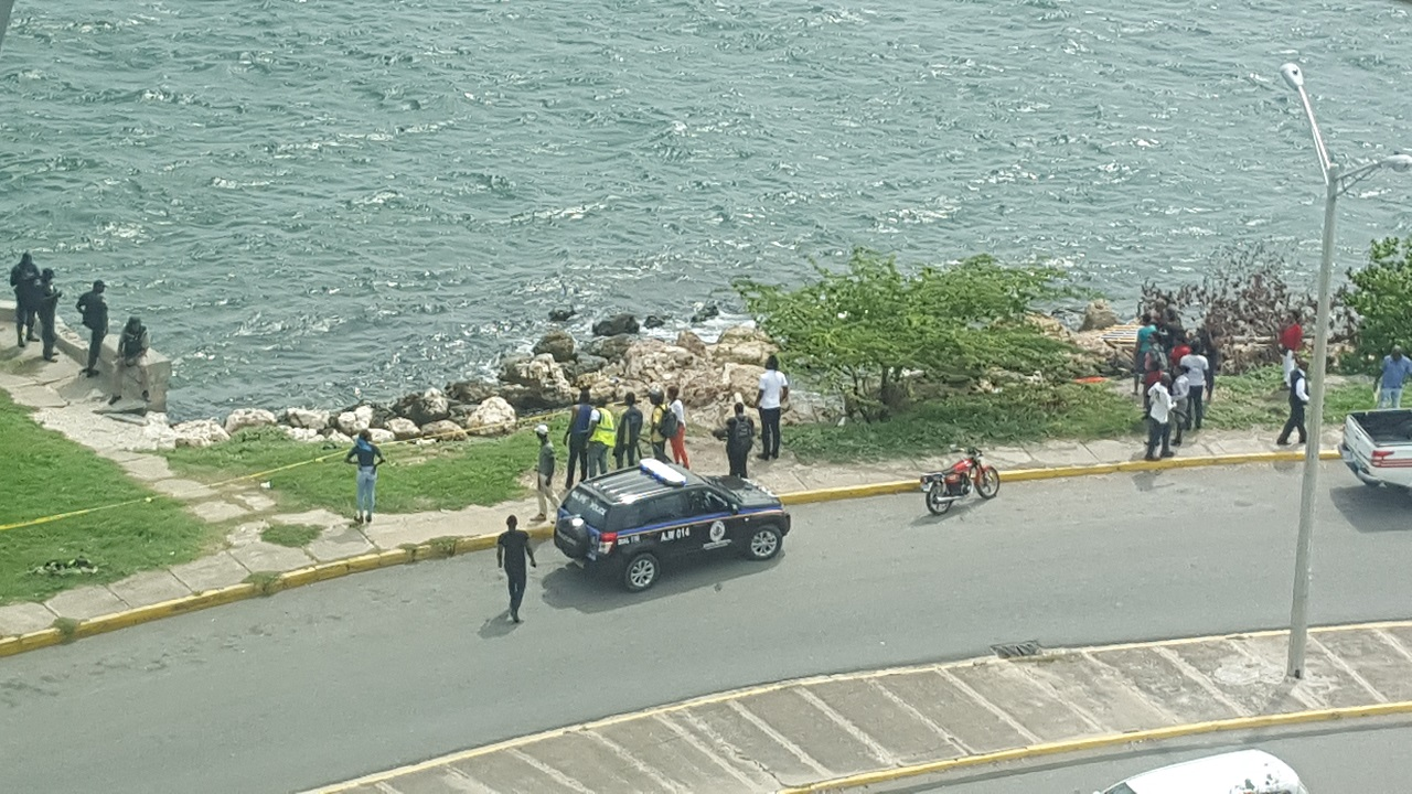 Police process the vicinity where the body of a man was found on Friday amid curious onlookers. (PHOTO: Marlon Reid)