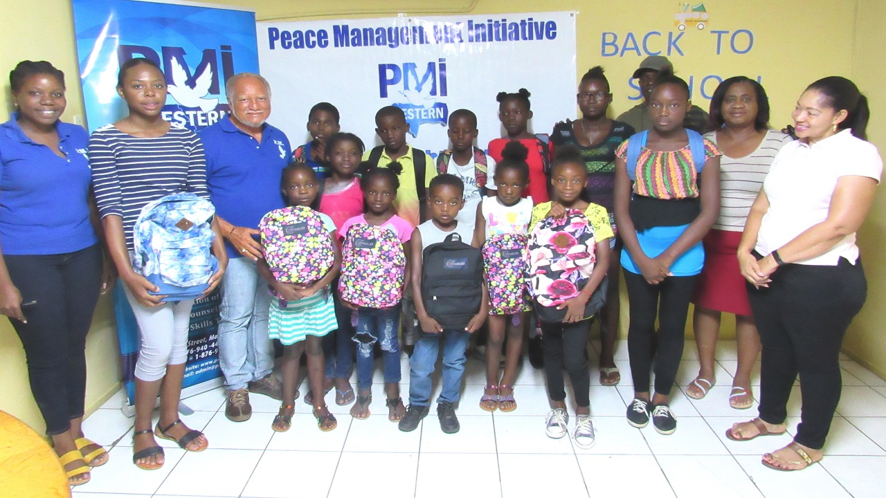 Vice Chairman of PMI Western, Pastor Richard Keane (third left), stands with students from the communities of Adelphi, Norwood and Anchovy and members of the PMI Western staff following the presentation of back-to-school items to the students.