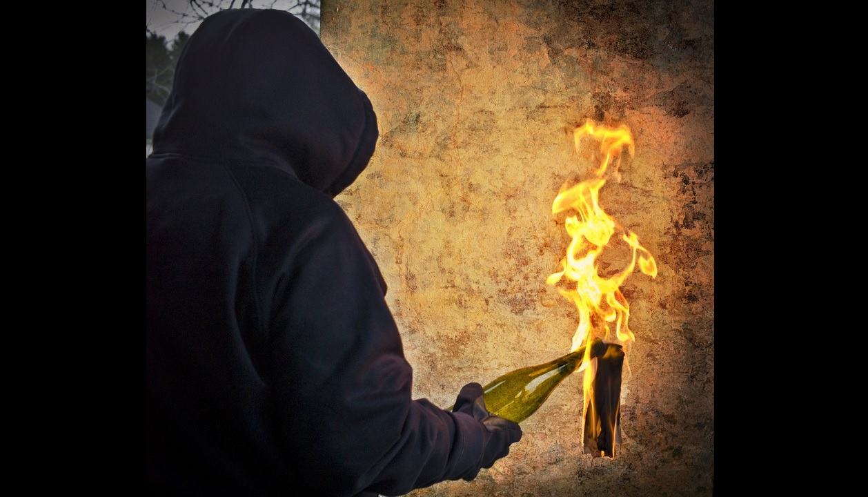 Stock image of a man with a Molotov cocktail bomb.