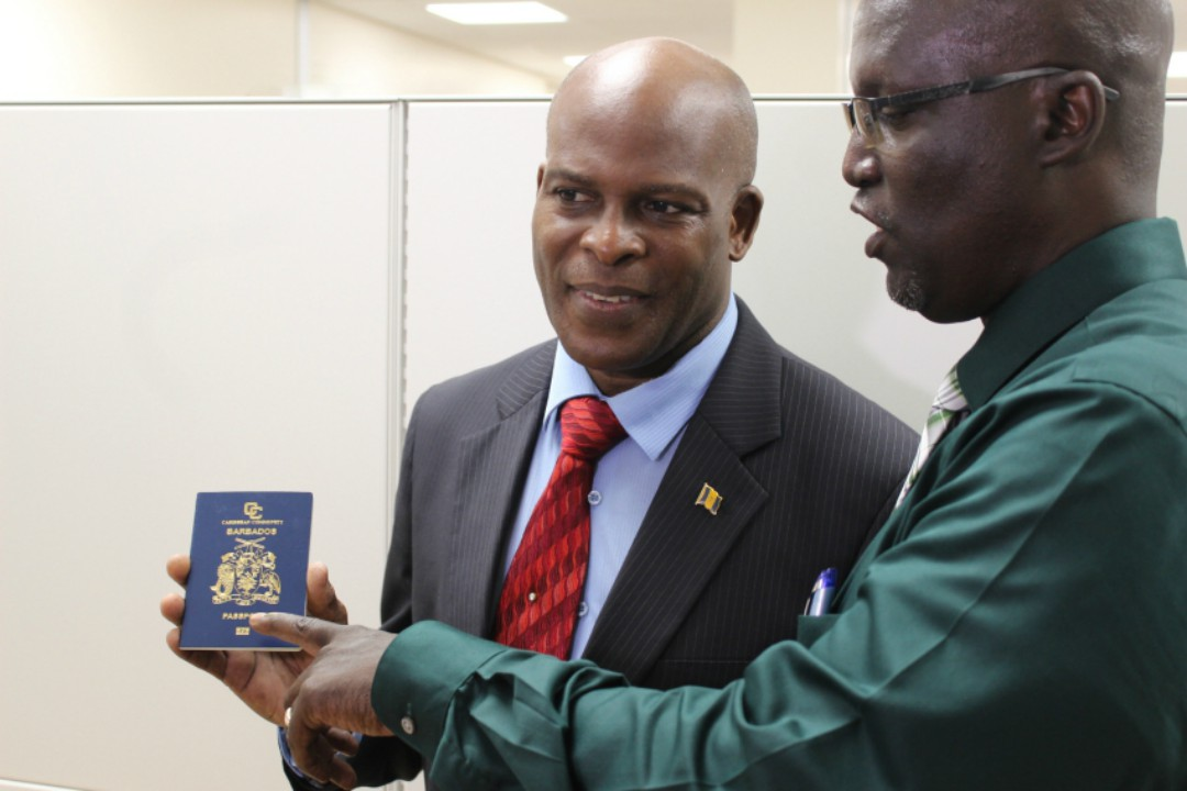 Minister of Home Affairs, Edmund Hinkson and Chief Immigration Officer, Wayne Marshall, showing one of the new e-passports, which are biometrically enabled with a chip and antenna in the cover. (M.Elcock/BGIS)