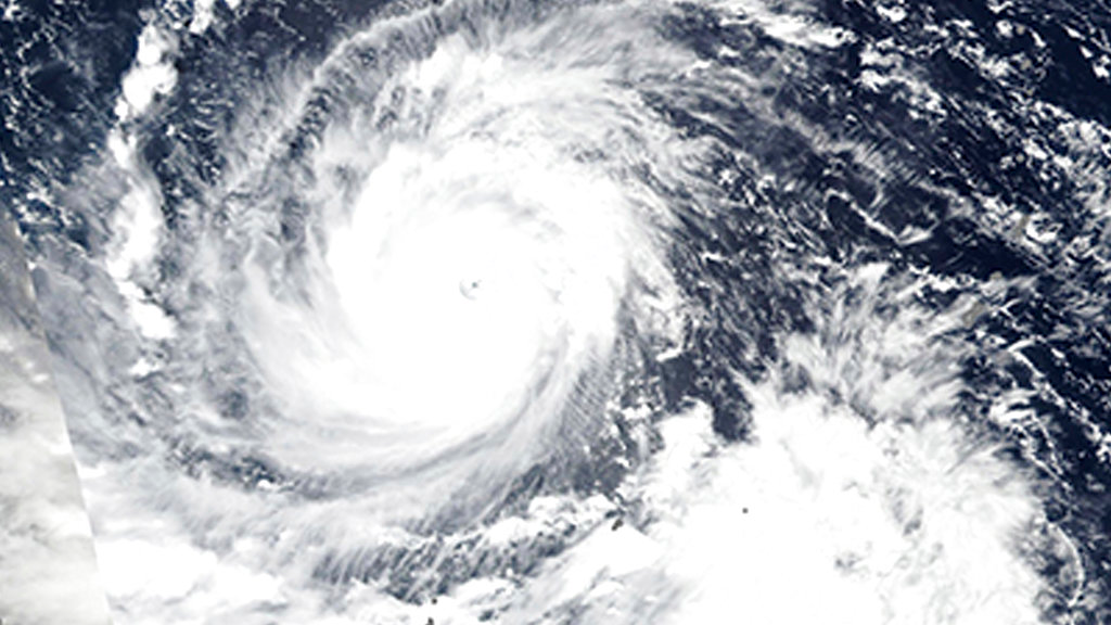 In this Wednesday, Sept. 12, 2018, NASA satellite image, Super Typhoon Mangkhut churns west towards the Philippines. Philippine officials have begun evacuating thousands of people in the path of the most powerful typhoon this year, closing schools and readying bulldozers for landslides. (Lauren Dauphin/NASA Earth Observatory via AP)