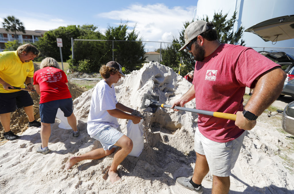 Walker Townsend at right from the Isle of Palms S.C. fills a sand bag while Dalton Trout in center holds the bag at the Isle of Palms municipal lot where the city was giving away free sand in preparation for Hurricane Florence at the Isle of Palms S