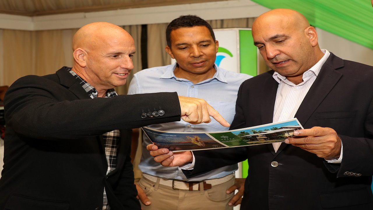 KLE CEO Gary Matalon (left), KLE Chairman David Shirley (centre) and Sagicor Group CEO Christopher Zacca (right) examine a brochure at the SPS hosted Sip and View event.