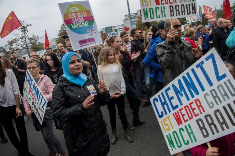 Des manifestants arborent les portraits de victimes de migrants pendant un rassemblement organisé par le parti anti-immigration AfD le 1er septembre 2018 à Chemnitz