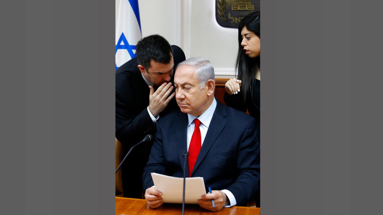Israeli Prime Minister Benjamin Netanyahu listens to his spokesman David Keyes as he opens the weekly cabinet meeting at his Jerusalem office. (Gali Tibbon/Pool via AP, File)