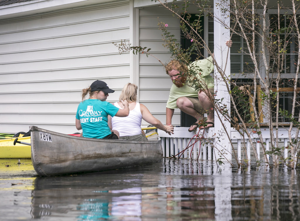 David Covington jumps from a porch railing to his canoe along with Maura Walbourne and her sister Katie Walborne in Conway, South Carolina. (Jason Lee/The Sun News via AP)