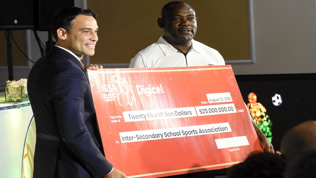 Justin Morin (left), CEO of Digicel Jamaica, presents a symbolic cheque for $25 million to Dr Walton Small, President of the Inter-Secondary Schools Sports Association (ISSA) at the launch of the 2018 schoolboy football season at the Terra Nova hotel in St Andrew on Wednesday.  Digicel will invest $75 million over three years as title sponsors for the urban area Manning Cup and Walker Cup knockout competitions. (Photos: Marlon Reid).