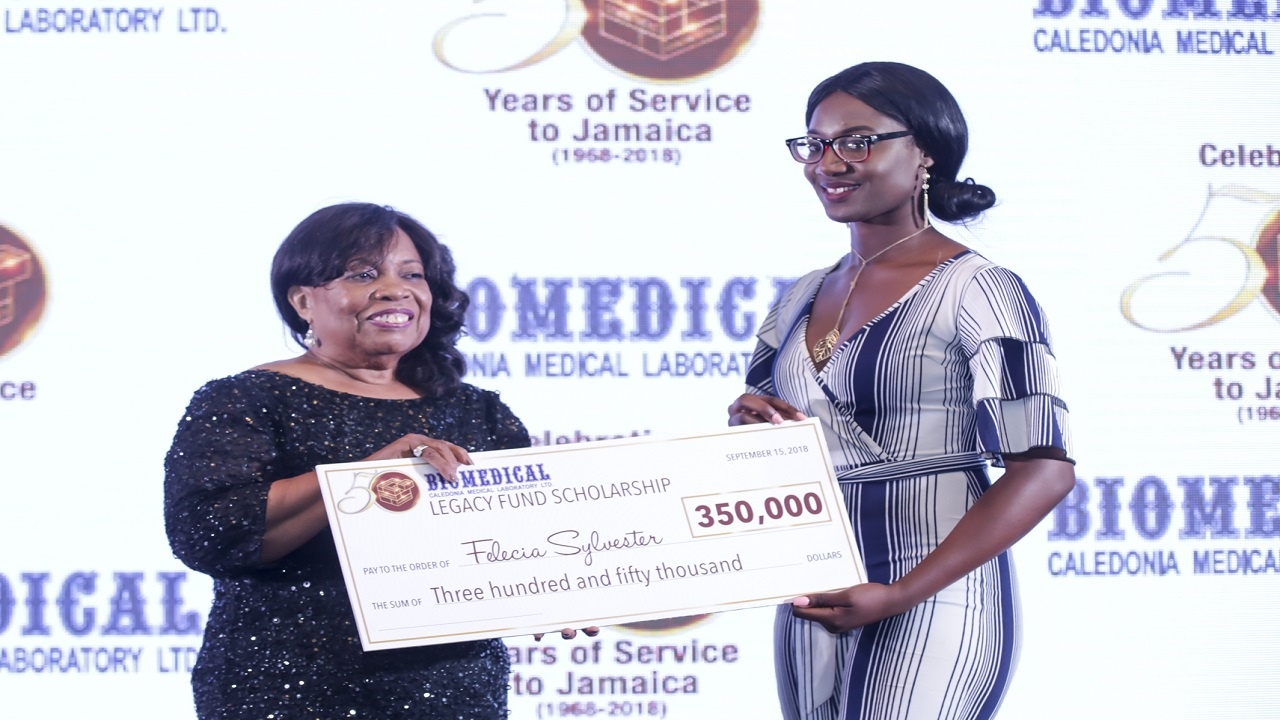 Barbara Hendriks (left) Managing Director, Biomedical Caledonia Medical Laboratory presents Felicia Sylvester (right) with a symbolic scholarship cheque, during the company's anniversary awards gala, held in Kingston recently.