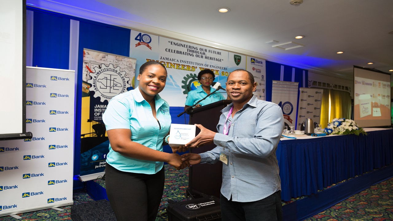 Shanoy Coombs (left), Communication and Events Consultant presents Courtney Newman, Engineer at Petrojam with a water saving device at Engineers' Week 2018, which was held on recently at the Knutsford Court Hotel in Kingston.