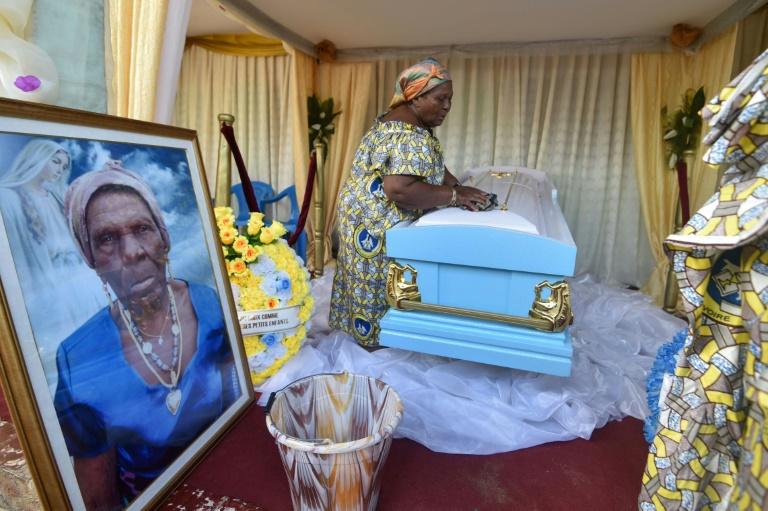 Les petites-filles de la centenaire décédée Anne M'Boua Ahoutié lui rendent hommage lors de son enterrement à Adjakoutié, un petit village à l'ouest d'Abidjan, le 3 août 2018
