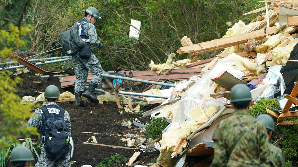 Japan Self-Defense Forces members search missing persons at the site of a landslide triggered by an earthquake in Atsuma town, Hokkaido, northern Japan, Friday, Sept. 7, 2018. A powerful earthquake hit wide areas on Japan's northernmost main island of Hokkaido early Thursday, triggering landslides as well as causing the loss of power. (AP Photo/Eugene Hoshiko)