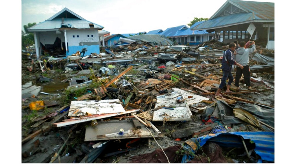 Indonesian men survey the damage following earthquakes and a tsunami in Palu, Central Sulawesi, Indonesia, Saturday, Sept. 29, 2018.