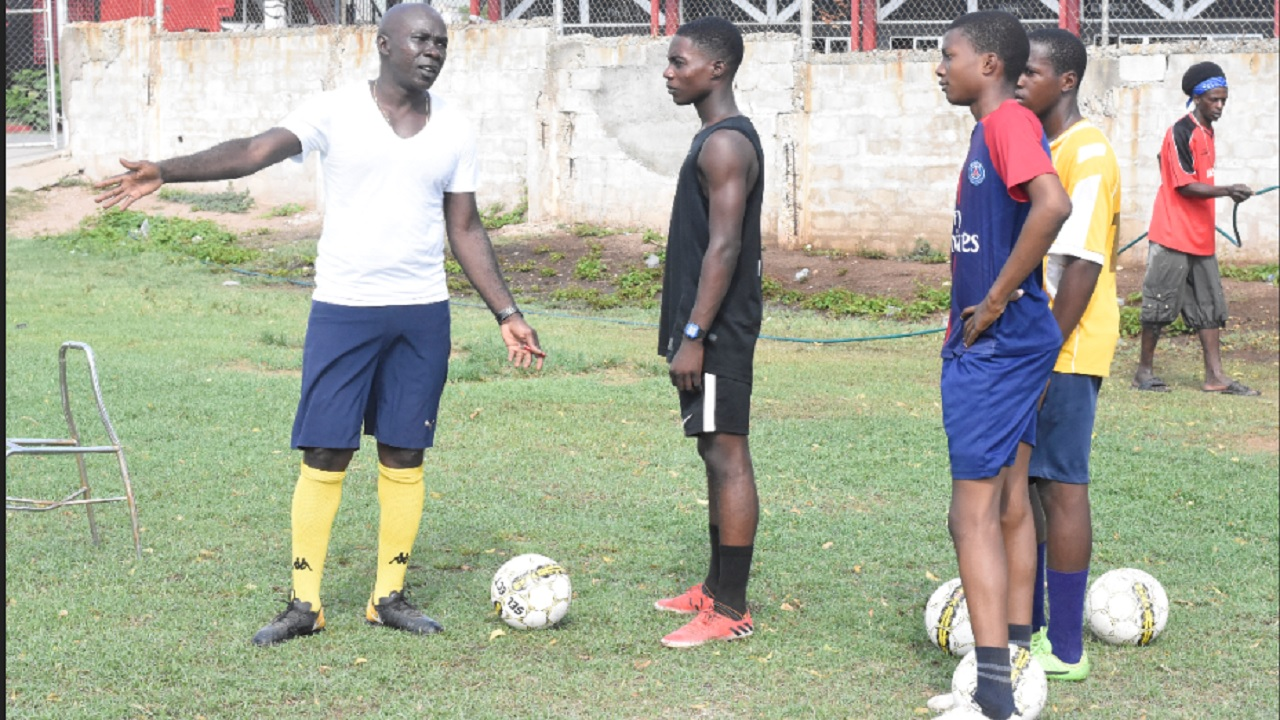 Former national player Walter Boyd (left) takes time out to speak with members of Charlie Smith Manning Cup football team during a training session at the school on Thursday, September 6. (PHOTOS: Marlon Reid).