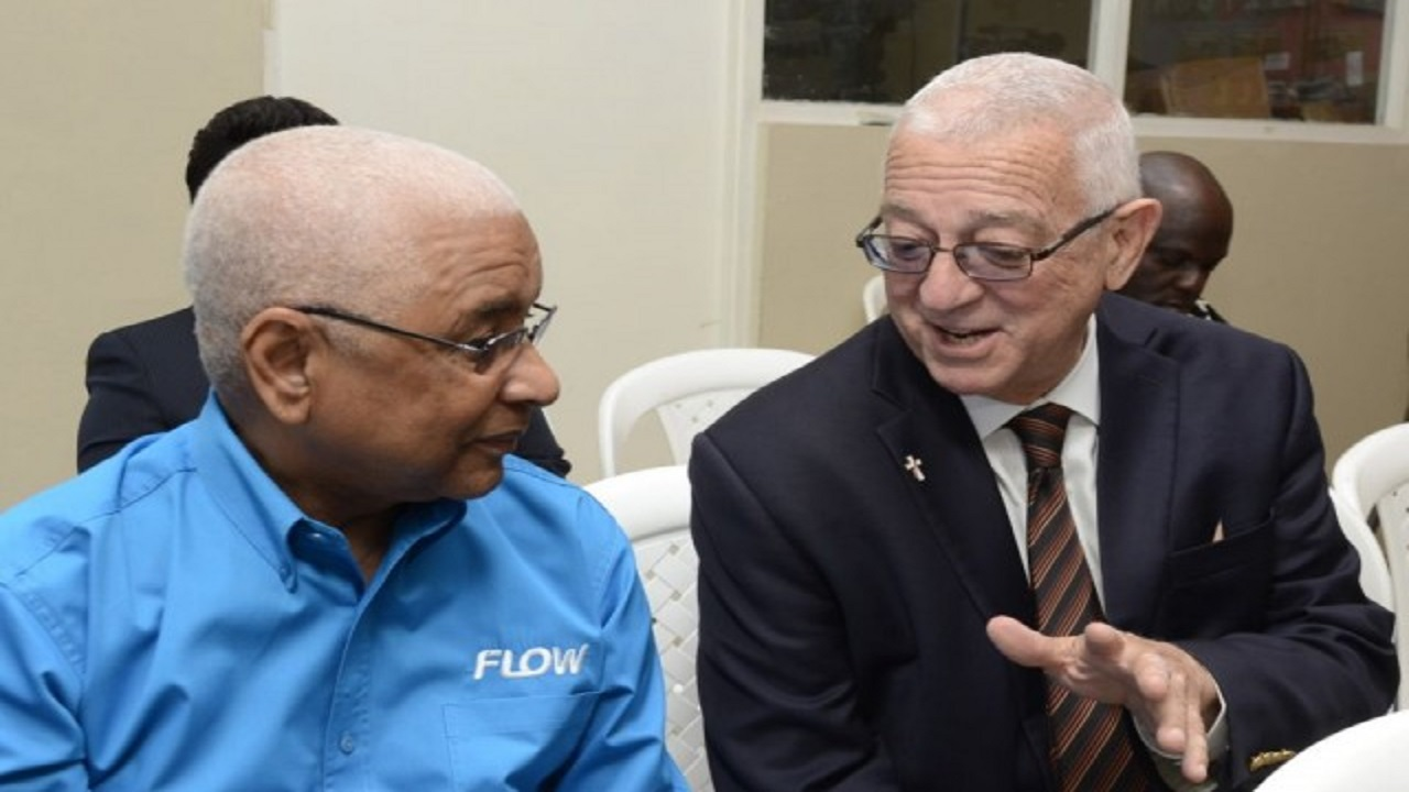 Flow Foundation's Executive Chairman, Errol K Miller (left), pictured in 2016 in the company of then Education Minister, Rev Ronald Thwaites.