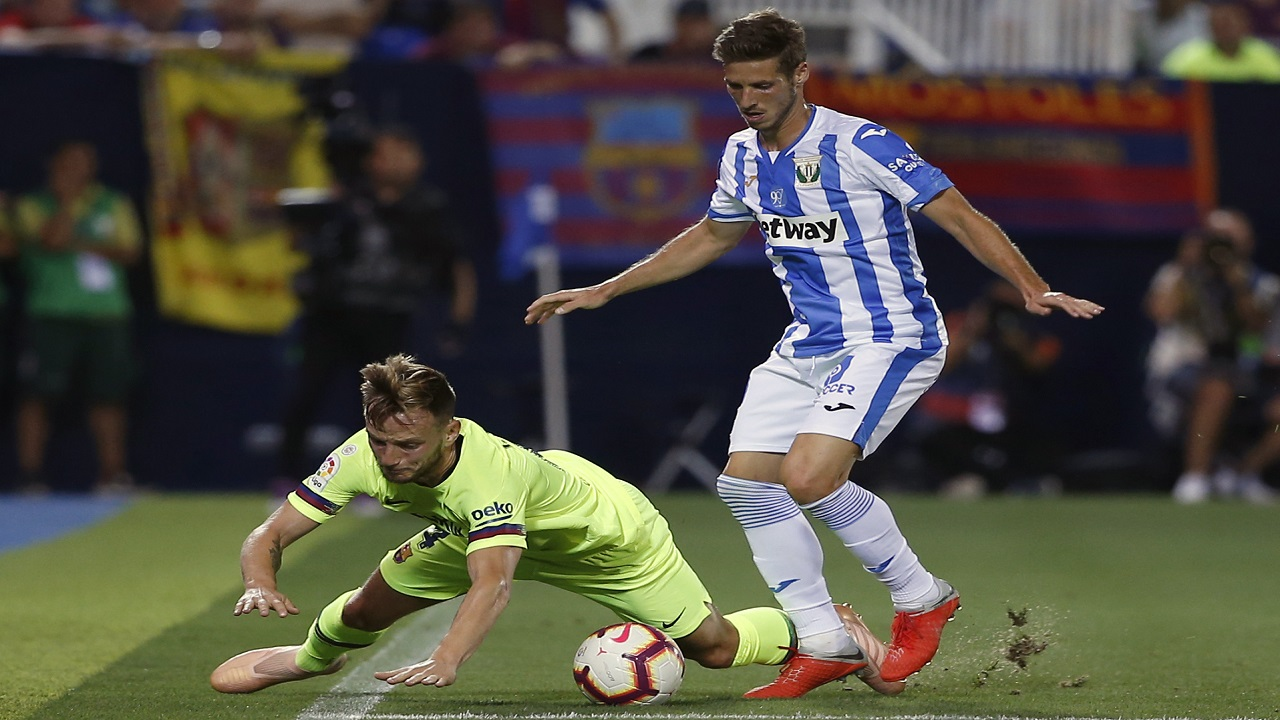 Barcelona's Ivan Rakitic, left, duels for the ball against Leganes' Alexander Szymanowski during their Spanish La Liga football game at the Butarque stadium in Leganes, Spain, Wednesday, Sept. 26, 2018.