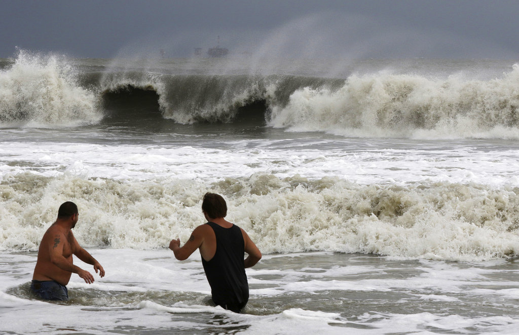 John Cunningham, left, and Hunter Shows, right, watch the waves crash from Tropical Storm Gordon on Tuesday, Sept. 4, 2018, in Dauphin Island, Ala. (AP Photo/Dan Anderson)