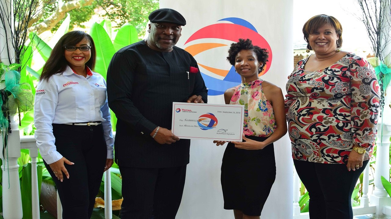 Melissa Anderson, human resources manager, Total Jamaica, looks on as Chris Okonmah, managing director, Total Jamaica, presents 2018 scholarship winner Gabrielle Buddoo with her bursay. At right is Lisa Vasciannie, lecturer, international relations and coordinator, French-Caribbean Programme, University of the West Indies