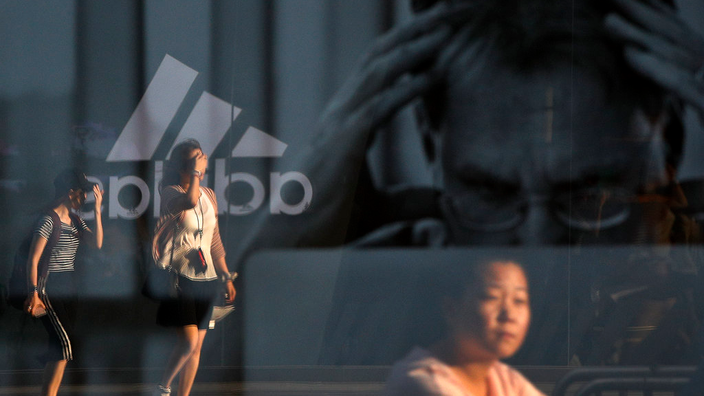 "Women are reflected on an advertisement for Apple's MacBook computer on display near a shopping mall in Beijing, Thursday, Sept. 6, 2018. China's government says it is ready to retaliate if U.S. President Donald Trump goes ahead with plans for another tariff hike on Chinese goods. The Commerce Ministry expressed confidence it can maintain ""steady and healthy"" economic growth despite their spiraling trade battle. (AP Photo/Andy Wong)"
