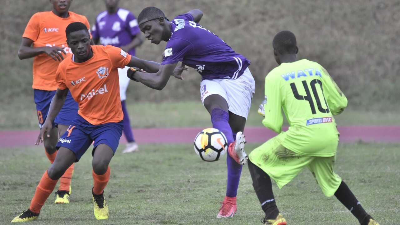 Kingston College defender Darnell Williams strikes the ball towards goal during his team's clash with Dunoon on Monday. KC won the match 8 - 0. (PHOTOS: Marlon Reid)