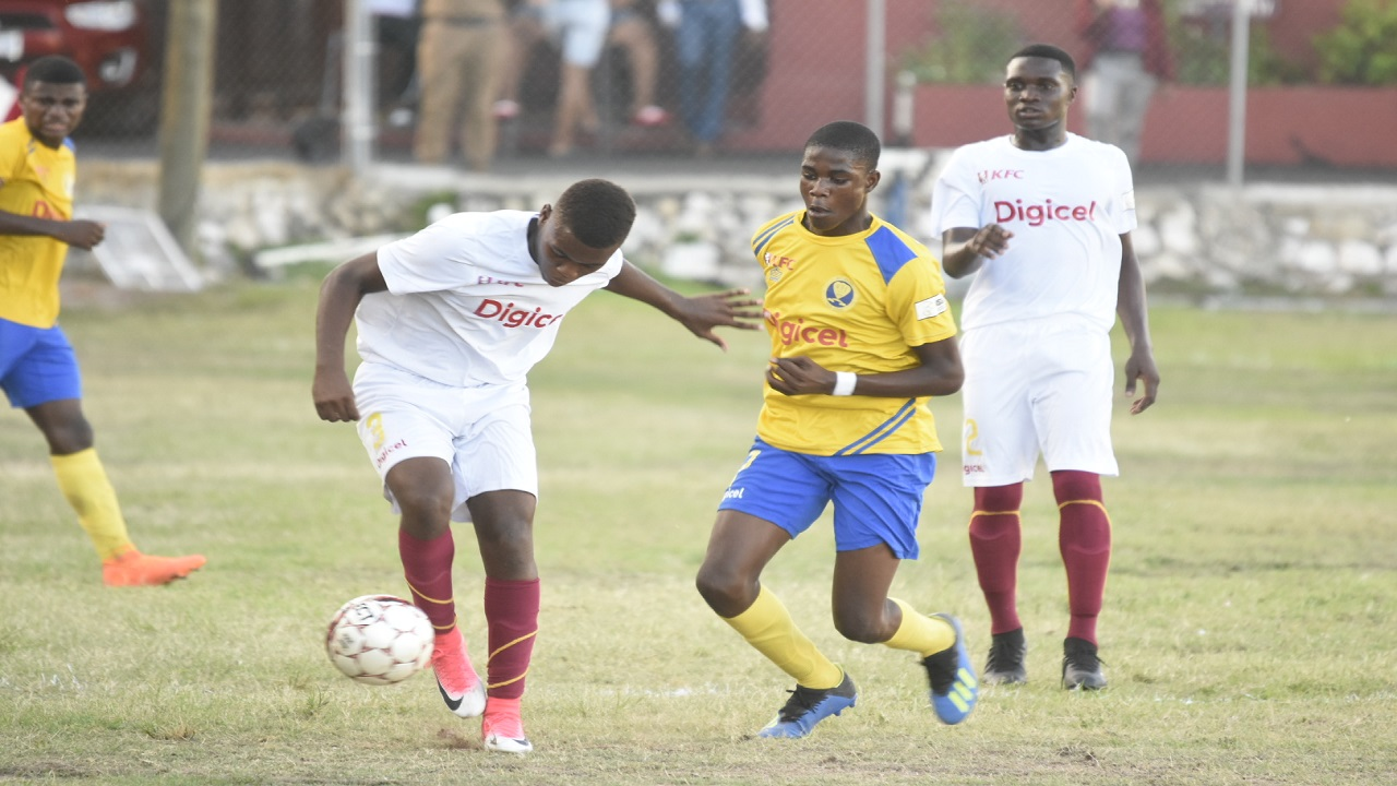 A Wolmer's player shields the ball from his Waterford High opponent in a Manning Cup match last week  which Wolmer's won 2 - 0.