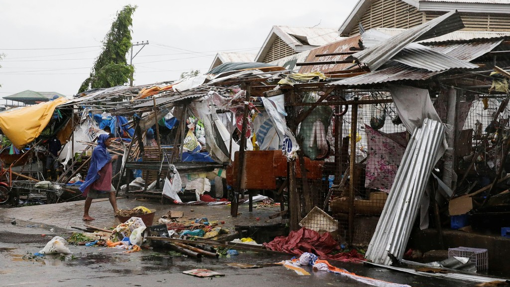 A resident looks at market stalls destroyed by strong winds as Typhoon Mangkhut barreled across Tuguegrao city in Cagayan province, northeastern Philippines on Saturday, Sept. 15, 2018. The typhoon slammed into the Philippines northeastern coast early Saturday, it's ferocious winds and blinding rain ripping off tin roof sheets and knocking out power, and plowed through the agricultural region at the start of the onslaught. (AP Photo/Aaron Favila)