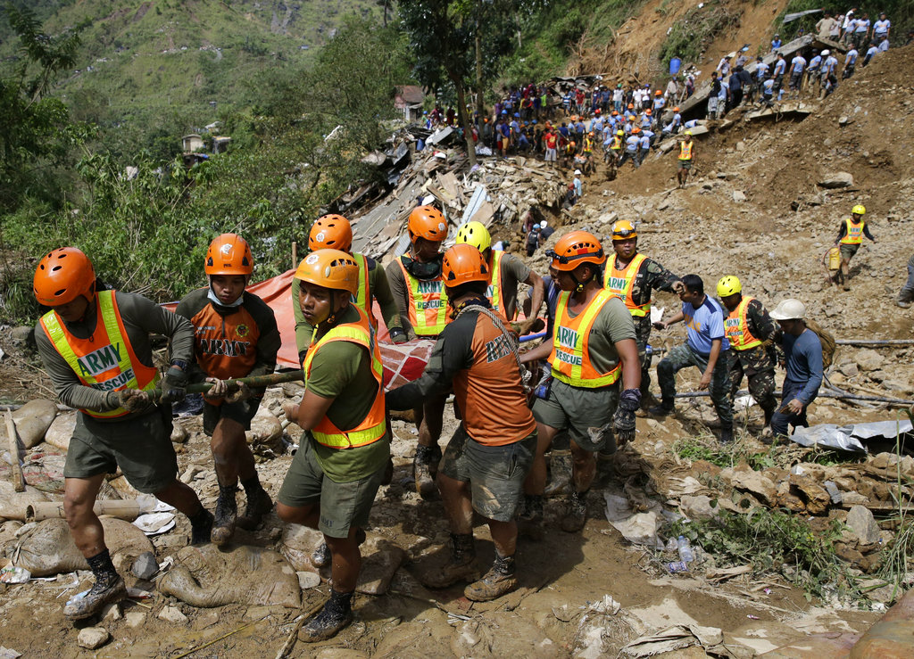 Rescuers carry a body recovered from a landslide caused by Typhoon Mangkhut in Itogon, Benguet province, northern Philippines on Monday, Sept. 17, 2018. Itogon Mayor Victorio Palangdan said that at the height of the typhoon's onslaught Saturday afternoon, dozens of people, mostly miners and their families, rushed into an old three-story building in the village of Ucab. (AP Photo/Aaron Favila)