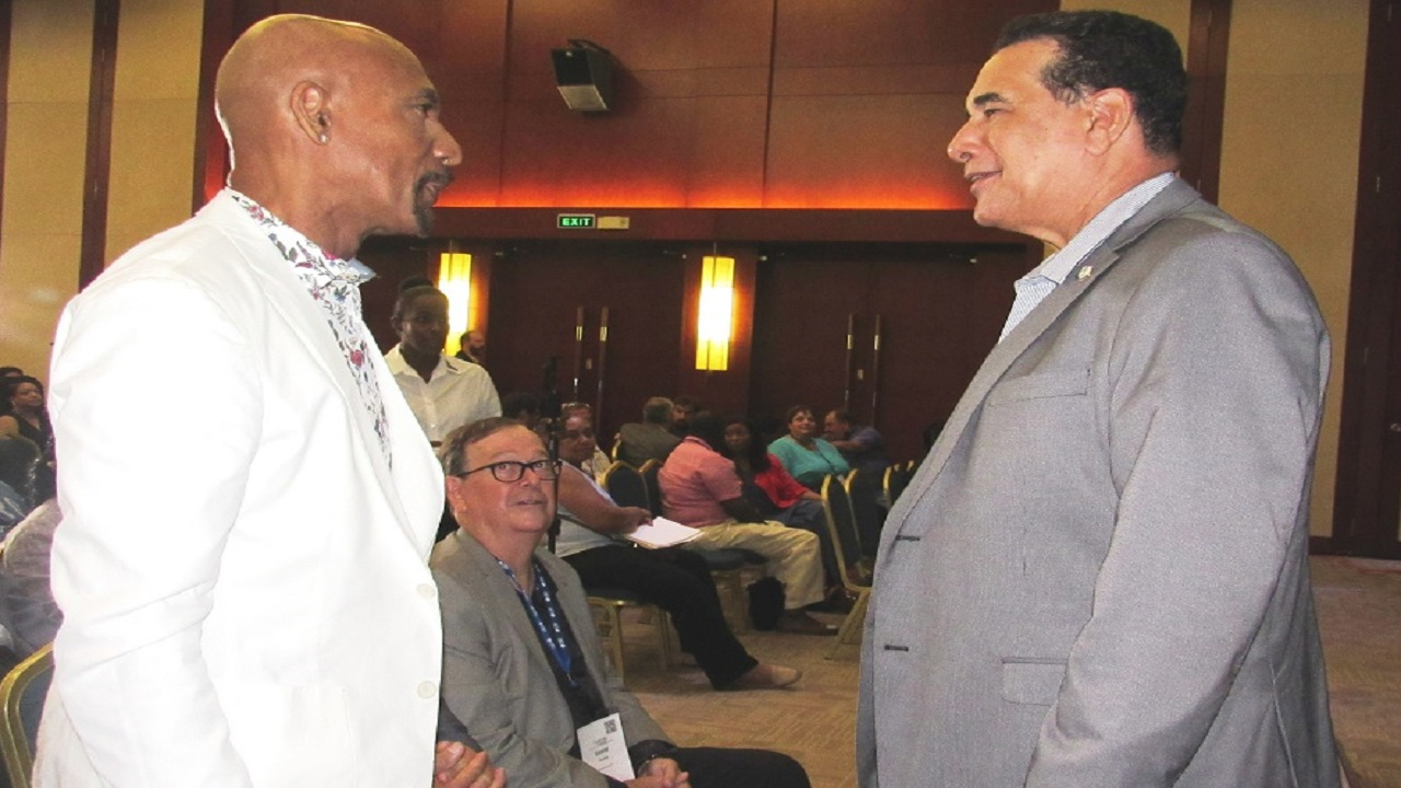 Mayor of Montego Bay, Homer Davis (right) shares pleasantries with American television personality, Montell Williams during the 2018 CanEx conference at the Montego Bay Convention Centre in St James.