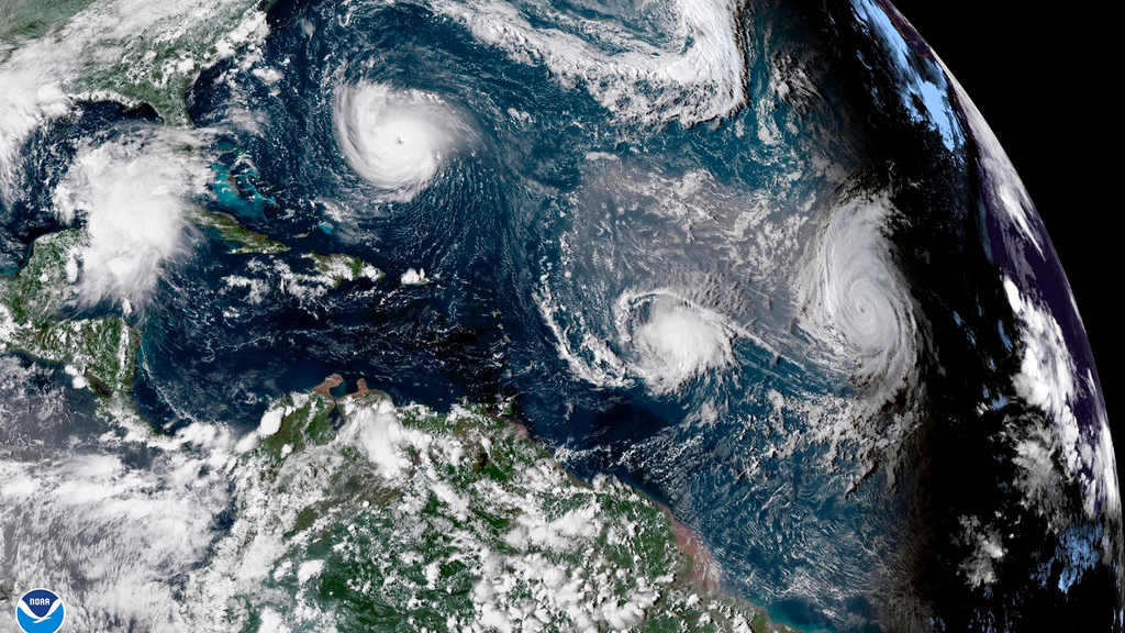 This enhanced satellite image made available by NOAA shows Tropical Storm Florence, upper left, in the Atlantic Ocean on Tuesday, Sept. 11, 2018 at 3:30 p.m. EDT. At center is Tropical Storm Isaac and at right is Hurricane Helene. (NOAA via AP)