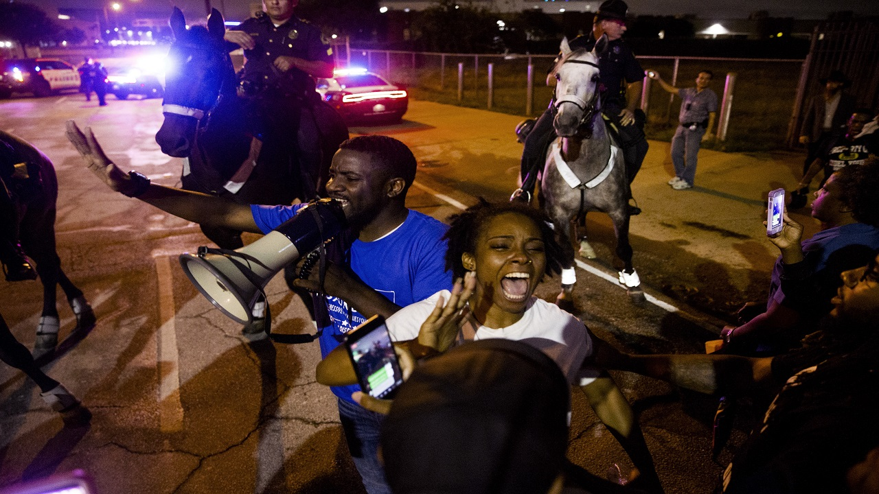 Dominique Alexander speaks to the protesters of the shooting of Botham Jean on Monday, Sept. 10, 2018 at the Jack Evans Police Headquarters in Dallas. (Shaban Athuman /The Dallas Morning News via AP)