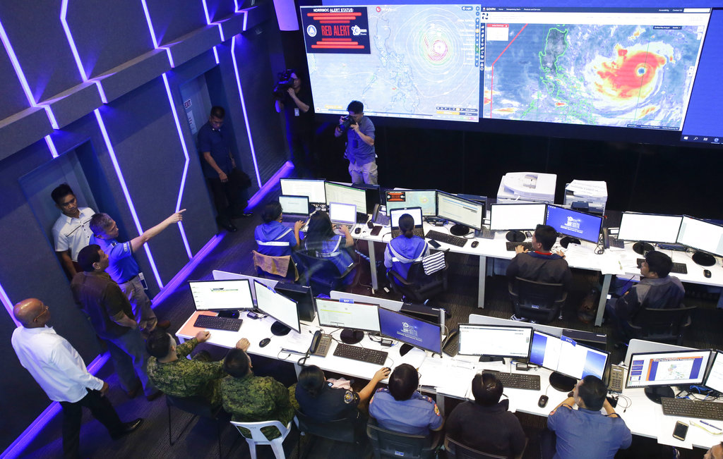 Philippine President Rodrigo Duterte, second from left, observes the National Disaster Risk Reduction and Management Council operation center in metropolitan Manila, Philippines on Thursday, Sept. 13, 2018.  (AP Photo/Aaron Favila)