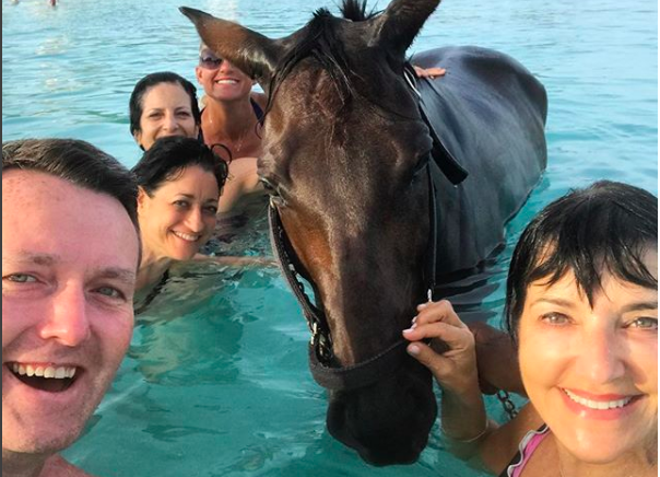 Meryl and friends from the Society of American Travel Writers having a dip in Carlisle Bay, Barbados, with a horse.