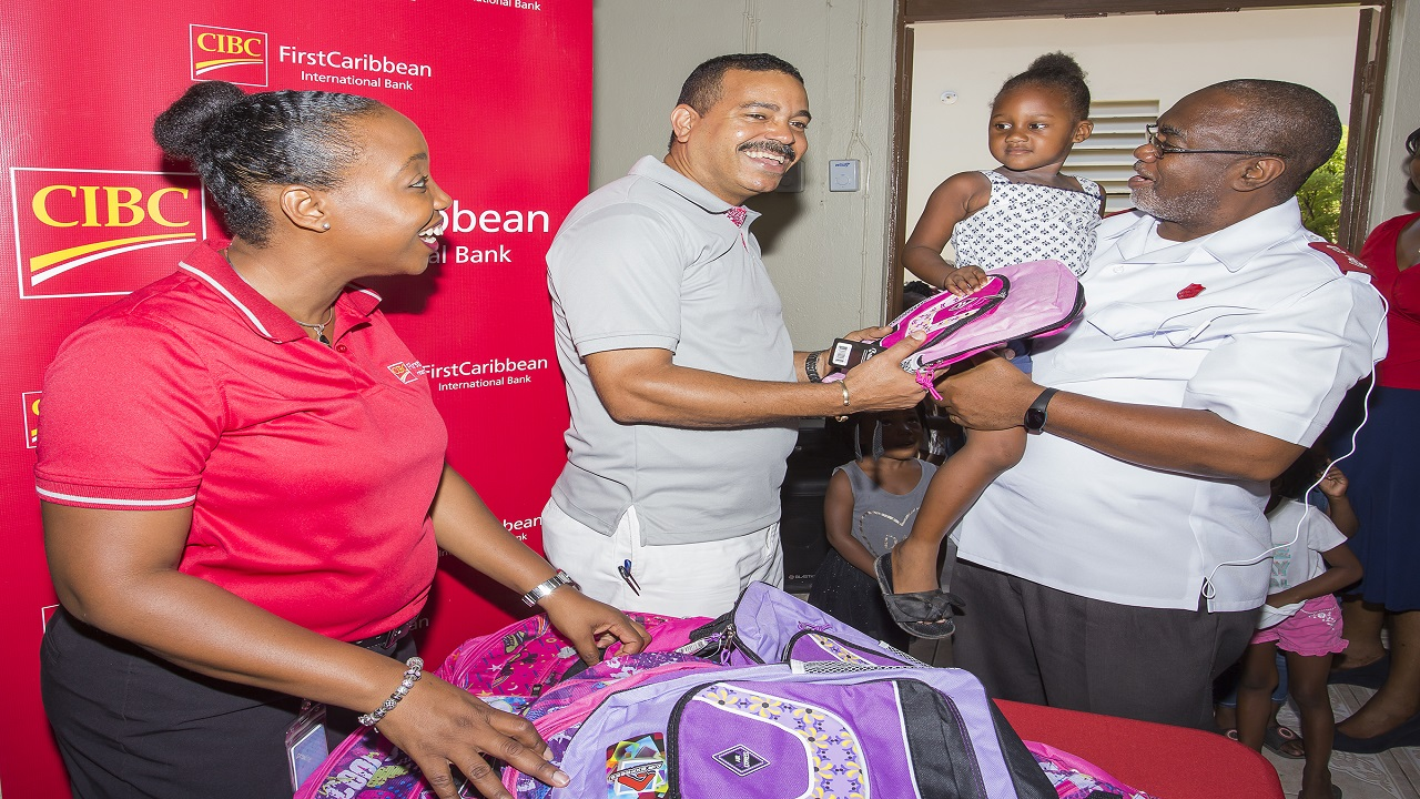 Renee Whitehorne (left), Marketing Manager and Nigel Holness (2nd left), Managing Director of the Bank with Major Oral Morris (right), Divisional Commander, Eastern Division, Salvation Army, and a young beneficiary of the Back to School Treat sponsored by the two entities in Jones Town.