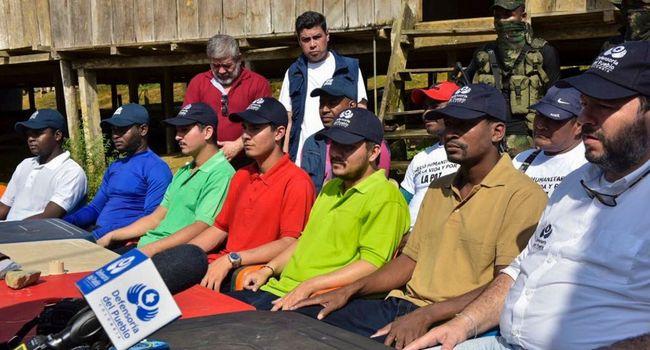Photo transmise par les services de l'Ombudsman colombien des otages libérés par la guérilla de l'ELN lors d'une conférence de presse avec l'Ombudsman Carlos Alfonso Negret (à droite), dans le département de Choco, le 12 septembre 2018.