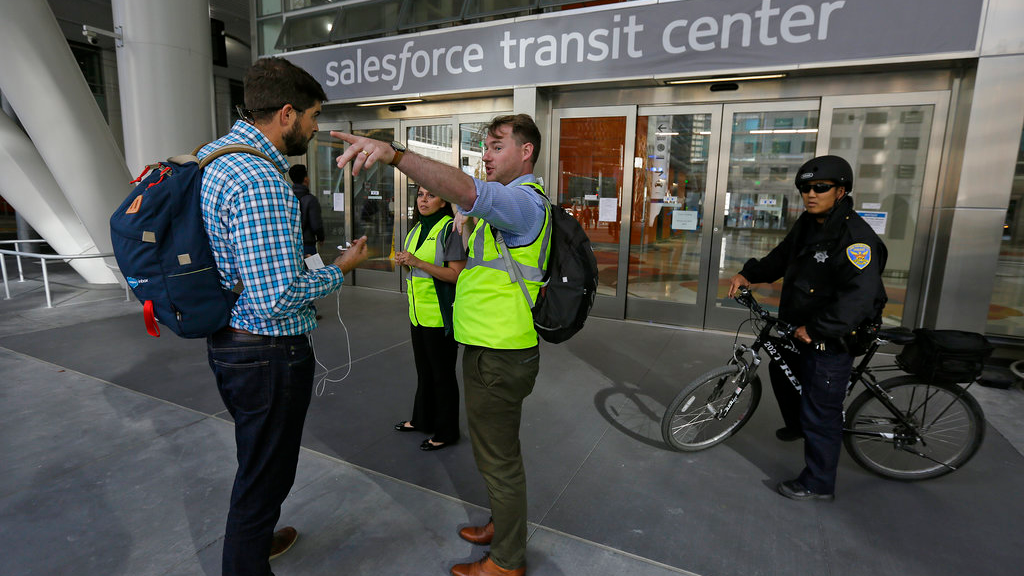 Mike Eshleman, with AC Transit, directs people away from the Salesforce Transit Center following its closure, Tuesday, Sept. 25, 2018, in San Francisco. San Francisco officials shut down the city's celebrated new $2.2 billion transit terminal Tuesday after discovering a crack in a support beam under the center's public roof garden. (AP Photo/Eric Risberg)