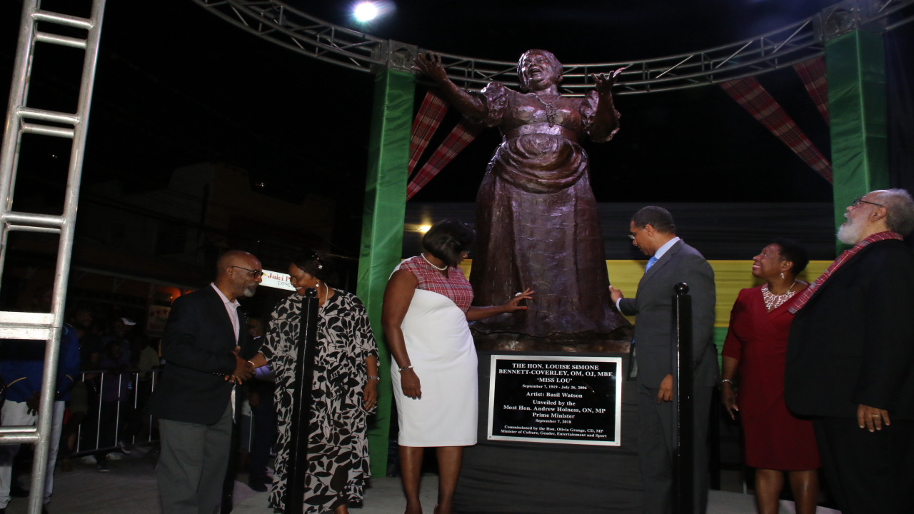 Prime Minister Andrew Holness (third right) and Juliet Holness (third left) touch the Miss Lou statue while Culture Minister Olivia 'Babsy' Grange (second right) and others look on at the unveiling of the sculpture last Friday in Gordon Town, St Andrew. (PHOTOS: Llewellyn Wynter)