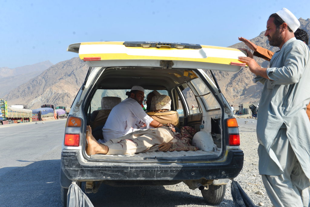 Men carry a dead body with a civilian vehicle in Momandara district of Nangarhar province, Afghanistan, Tuesday, Sept. 11, 2018. (AP Photo/Mohammad Anwar Danishyar)