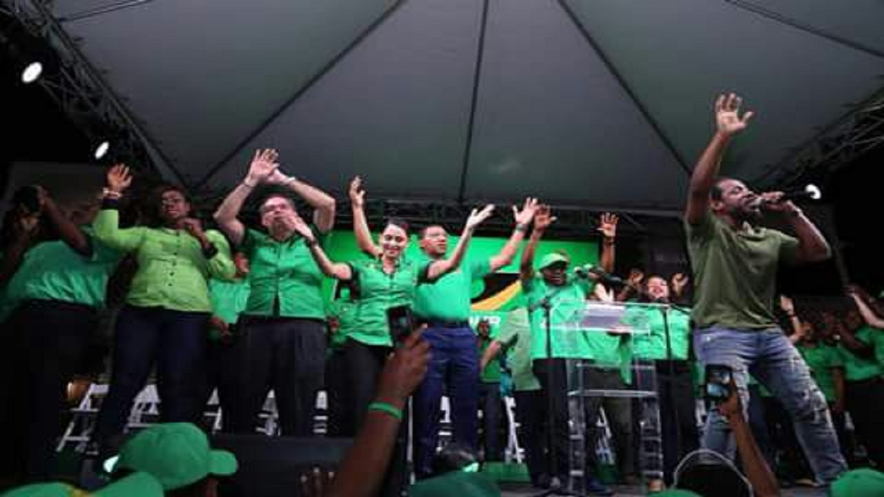 Wayne Marshall (far right) performs for the massive crowd at the JLP rally in Port Antonio on Sunday night. Ann Marie Vaz (fourth from left) enjoys the performance with her husband, Daryl Vaz (third from left), Prime Minister Andrew Holness (fifth from left) and other JLP members.