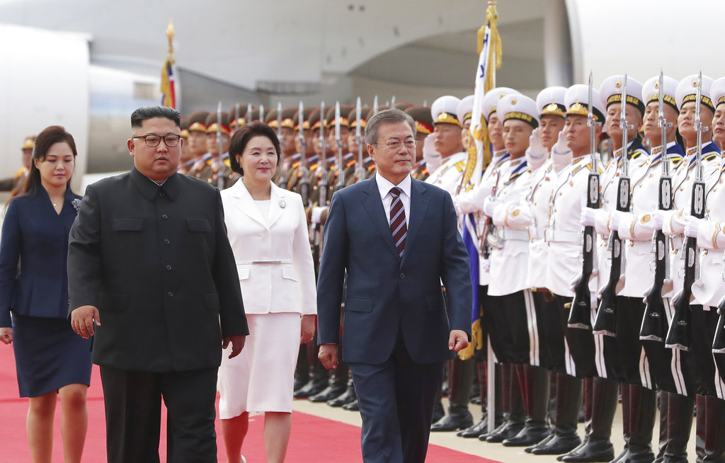South Korean President Moon Jae-in, front right, his wife Kim Jung-sook, North Korean leader Kim Jong Un, front left, and his wife Ri Sol Ju, left, inspect honor guard during a welcoming ceremony at Sunan International Airport in Pyongyang in North Korea, Tuesday, Sept. 18, 2018. (Pyongyang Press Corps Pool via AP)