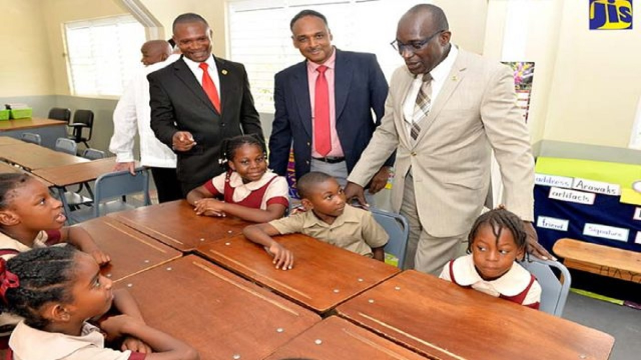 Minister of Education, Youth and Information, Senator Ruel Reid (right), interacts with students at Mineral Heights Primary School in Clarendon after a ceremony on Thursday (September 13) to officially hand over 12 new classrooms. Looking on (from left) are Principal of the school, Lanzeford Howell; and Managing Director, Jamaica Social Investment Fund (JSIF), Omar Sweeney. The new clarooms have facilitated the transition of the school from the shift system.