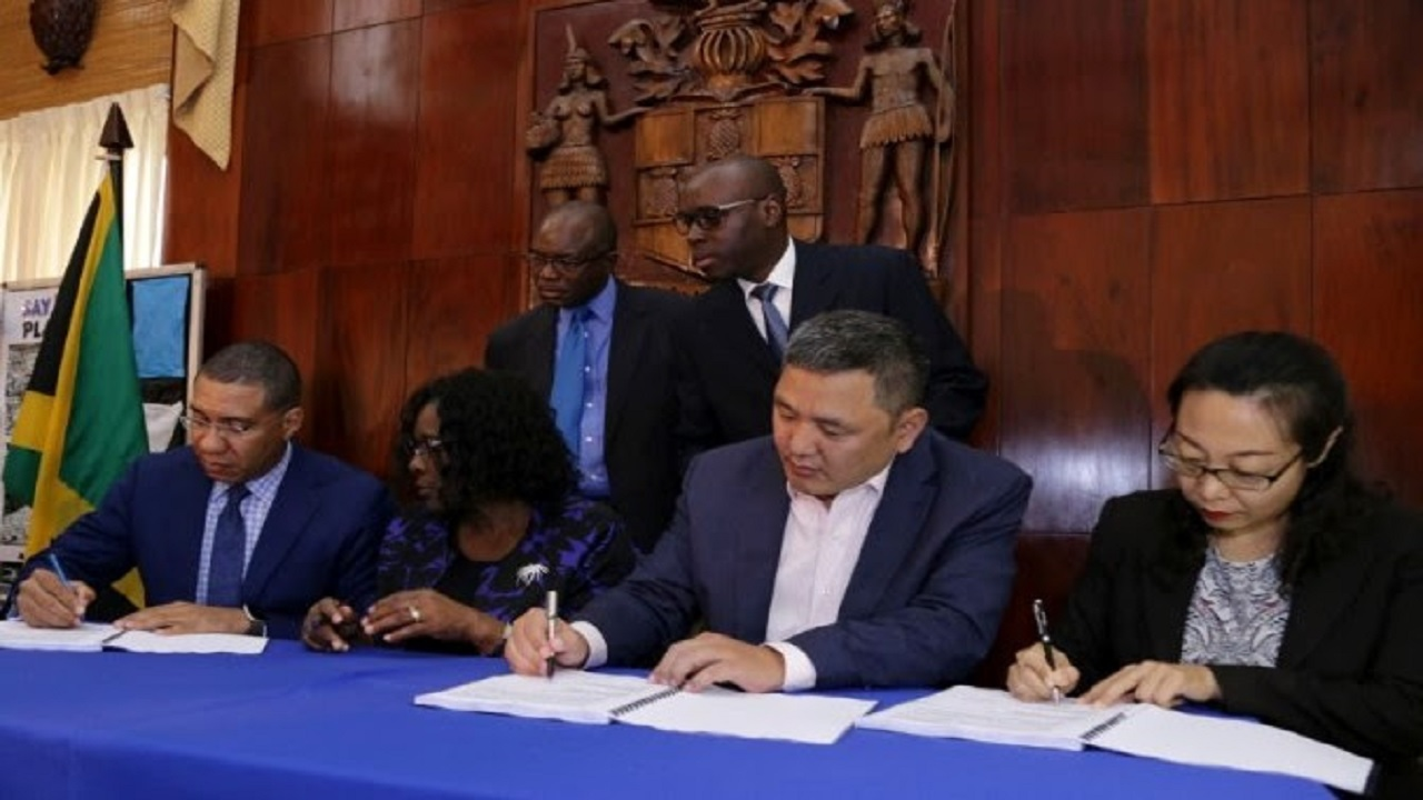Prime Minister Andrew Holness signs a contract agreement with China Harbour Engineering Company (CHEC) for the construction of a new road to bypass the Three Miles area valued at US$1 million. (PHOTO: OPM)