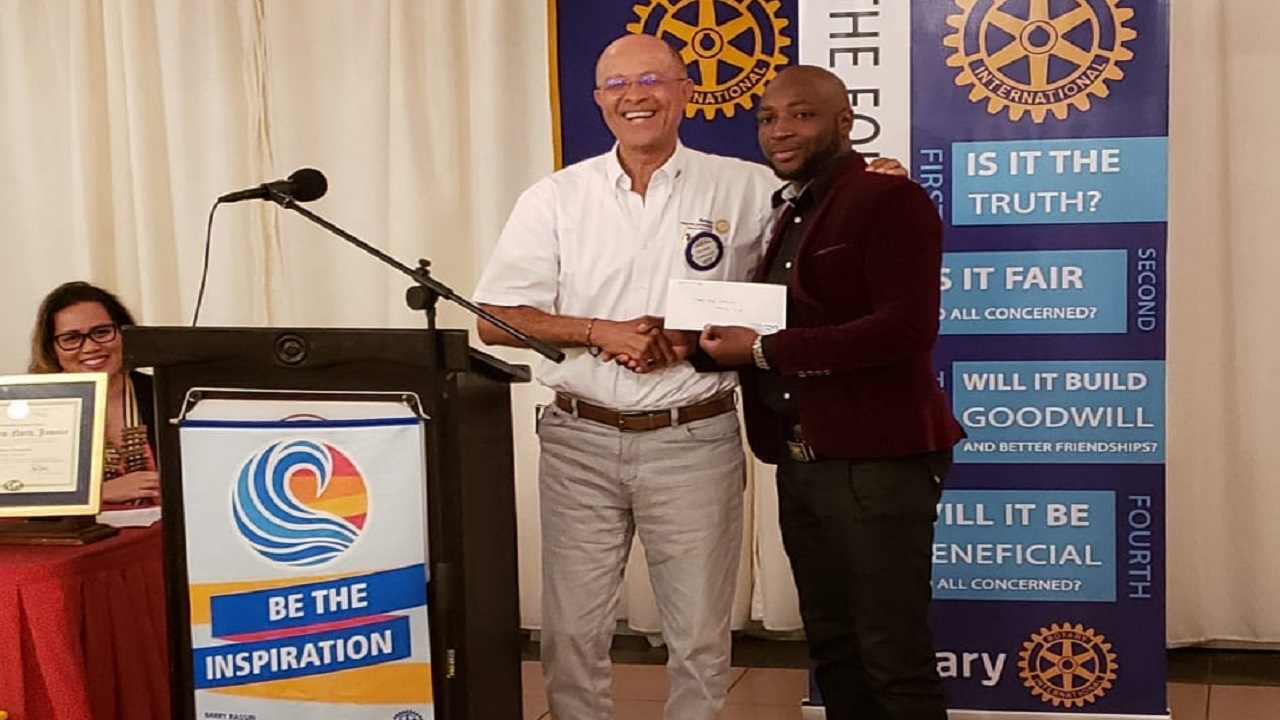 Donald Patterson (left), Director of the Rotary Club of St. Andrew North Education Foundation presents a cheque to Kieron Mitchell, father of award recipient from St. Mary now attends Westwood High School.