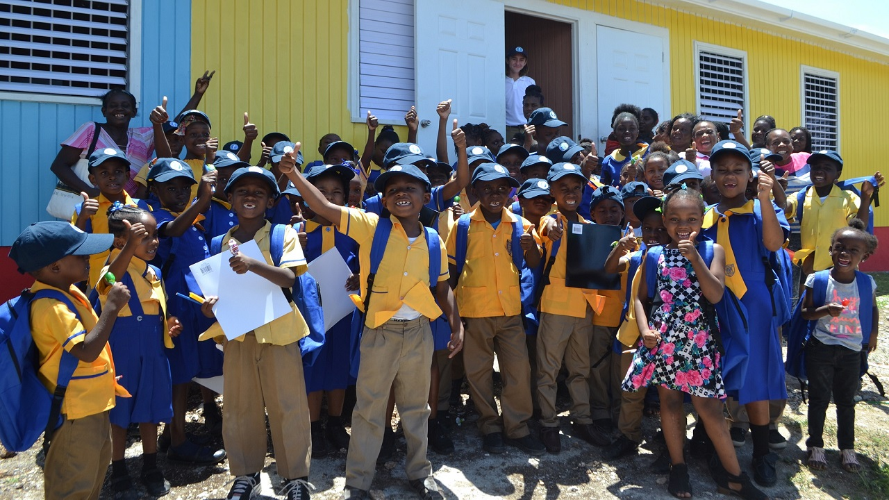 Rafe Cochran (by the door) shares in a group photo with students of the Runaway Bay All Age School moments after the ribbon cutting exercise for two new classroom blocks.