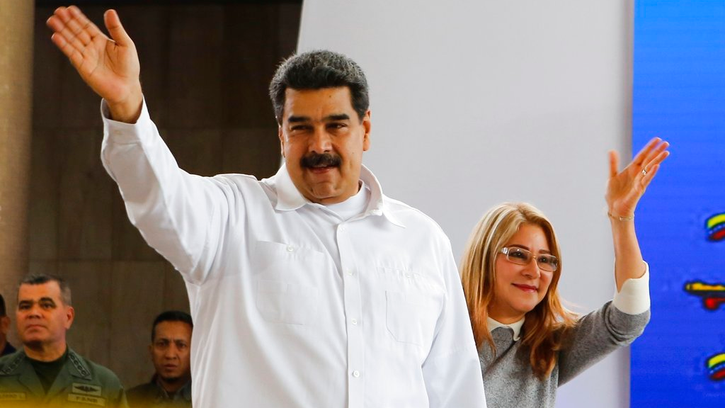 In this photo released by the Miraflores Press Office, Venezuela's President Nicolas Maduro, left, and his wife Cilia Flores greet supporters upon their arrival to a meeting with Colombian citizens that reside in Venezuela, In Caracas, Venezuela, Tuesday, Sept. 25, 2018.  (Miraflores Press Office via AP)
