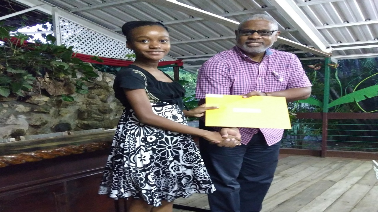 Former Mona Heights Primary School student Emily Williams, who now attends Campion College collects her award from AQuA Foundation Executive Director Nigel Pennycooke.